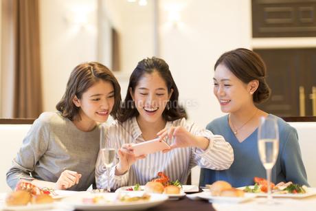 スマートフォンで料理を撮る3人の女性の写真素材 [FYI02970175]