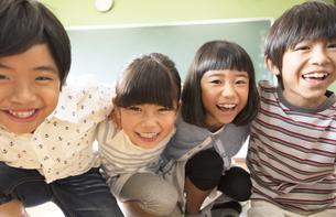 黒板の前で肩を組んで笑う子供たちの写真素材 [FYI02970184]