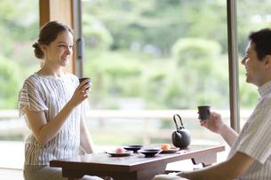 お茶を手に話しをする男女の外国人観光客の写真素材 [FYI02970194]