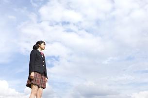 青空をバックに立つ女子高校生の写真素材 [FYI02970196]