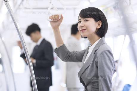 電車でつり革を持ち遠くを見つめるビジネス女性の写真素材 [FYI02970198]