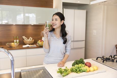 スムージーを手に微笑む女性の写真素材 [FYI02970204]