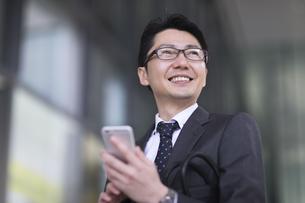 スマートフォンを持ち横を見るビジネス男性の写真素材 [FYI02970205]