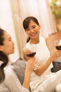 ソファーに座ってワインを手に笑い合う女性2人の写真素材 [FYI02970207]