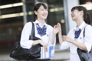 駅のホームで会話をする女子高校生たちの写真素材 [FYI02970227]