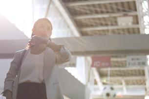 駅で時計を確認し周りを見るビジネス女性の写真素材 [FYI02970231]