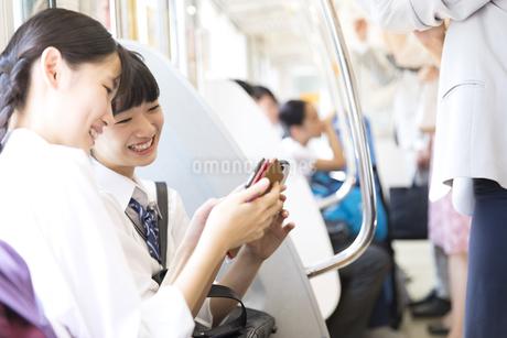 電車で友人と会話をする女子高校生たちの写真素材 [FYI02970237]