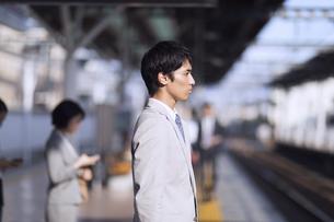 駅のホームで電車を待つビジネス男性の写真素材 [FYI02970238]
