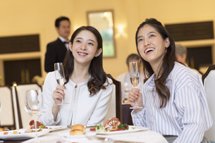 シャンパンを持ち遠くを見る2人の女性の写真素材 [FYI02970239]