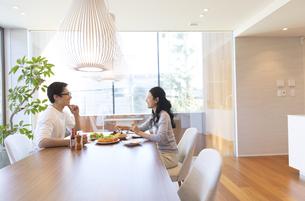 ダイニングテーブルで食事を楽しむ夫婦の写真素材 [FYI02970240]