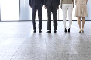 横並びで立つ4人のビジネス男女の後ろ姿の写真素材 [FYI02970251]