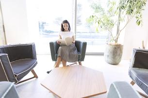 椅子に座り本を読む女性の写真素材 [FYI02970259]