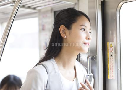 電車で外の景色を見つめるビジネス女性の写真素材 [FYI02970273]