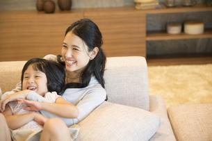 ソファーで戯れる母親と娘の写真素材 [FYI02970281]
