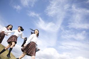 青空をバックに歩く女子高校生たちの写真素材 [FYI02970285]