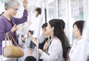 電車で座席を譲ろうとするビジネス女性の写真素材 [FYI02970299]