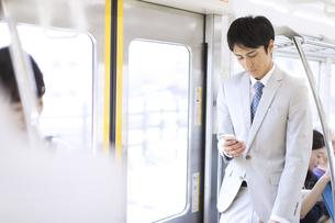 電車でスマホを操作するビジネス男性の写真素材 [FYI02970302]