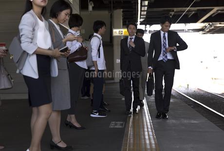 駅のホームを歩くビジネス男性の写真素材 [FYI02970313]