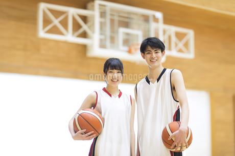 バスケットボールを持ち笑顔の男子学生と女子学生の写真素材 [FYI02970319]