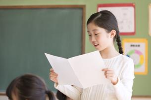 授業中に作文を読む小学生の女の子の写真素材 [FYI02970327]