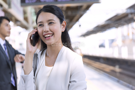 駅のホームで電話をするビジネス女性の写真素材 [FYI02970337]