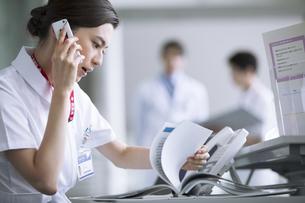 受付で電話対応をする女性看護師の写真素材 [FYI02970339]