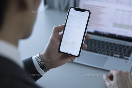 スマートフォンを見るビジネス男性の手元の写真素材 [FYI02970348]