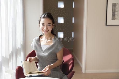 本を持ちカメラ目線の女性の写真素材 [FYI02970349]