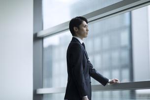 窓から遠くを見るビジネス男性の写真素材 [FYI02970365]