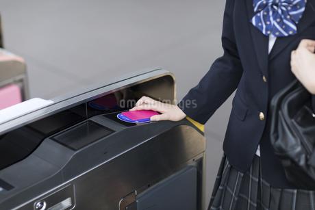 改札で定期券をかざす女子高校生の手元の写真素材 [FYI02970366]