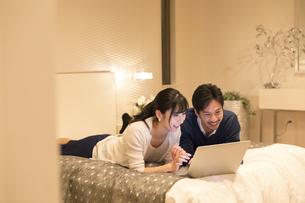 ベッドでパソコンを見る夫婦の写真素材 [FYI02970367]