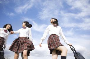青空をバックに歩く女子高校生たちの写真素材 [FYI02970369]