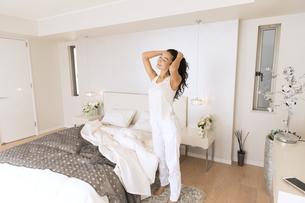 寝室で髪をかき上げる女性の写真素材 [FYI02970370]