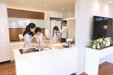 キッチンで料理を作る母親と姉妹の写真素材 [FYI02970378]