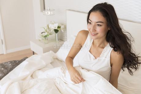ベッドに入り遠くを見つめる女性の写真素材 [FYI02970380]