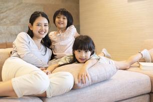 ソファーでくつろぐ母親と姉妹の写真素材 [FYI02970381]