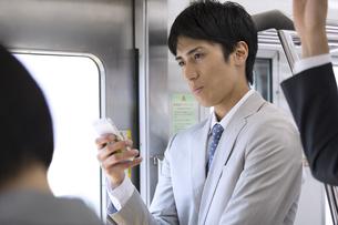 電車でスマホを操作するビジネス男性の写真素材 [FYI02970383]