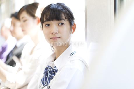 電車で遠くを見つめる女子高校生の写真素材 [FYI02970390]