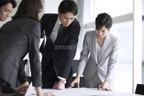 製図を使って打ち合わせをするビジネスマンの写真素材 [FYI02970393]
