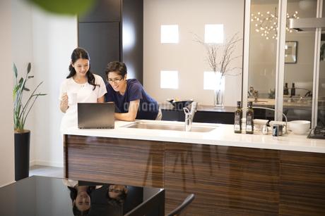 キッチンでパソコンを見る夫婦の写真素材 [FYI02970396]