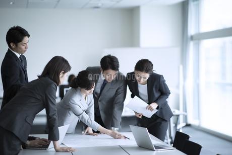 製図を使って打ち合わせをするビジネスマンの写真素材 [FYI02970401]