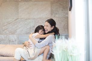 ソファーで戯れる母親と娘の写真素材 [FYI02970406]