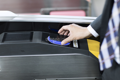 改札で定期券をかざすビジネス男性の手元の写真素材 [FYI02970412]