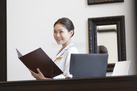 フロントに立つコンシェルジュの女性の写真素材 [FYI02970414]