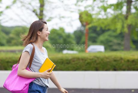 微笑みながら緑道を歩く女子学生の写真素材 [FYI02970460]