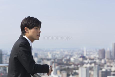 屋上でビル群を眺めるビジネス男性の写真素材 [FYI02970463]