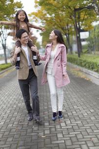 肩車して遊歩道を歩く家族の写真素材 [FYI02970464]