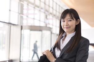 ビルのエントランスで微笑むビジネス女性の写真素材 [FYI02970470]