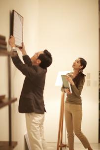 壁に写真を飾る男性とそれを見る女性の写真素材 [FYI02970503]