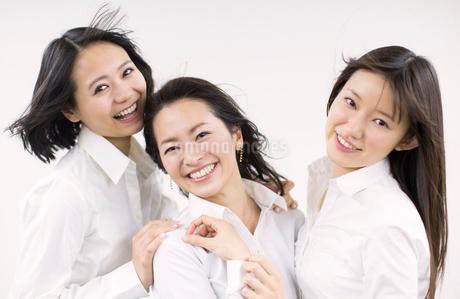 風を受けながら笑う女性3人の写真素材 [FYI02970510]